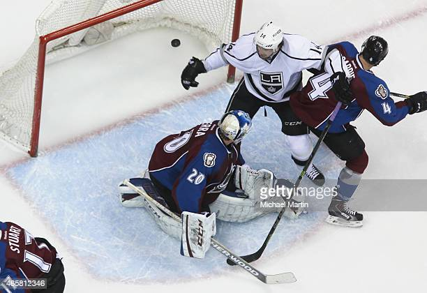 Goaltender Reto Berra and Tyson Barrie of the Colorado Avalanche watch as the puck enters the net while Justin Williams of the Los Angeles Kings...