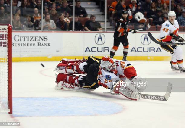 Goaltender Reto Berra of the Calgary Flames dives but can't make the save on a shot by Sami Vatanen of the Anaheim Ducks in the first period at Honda...