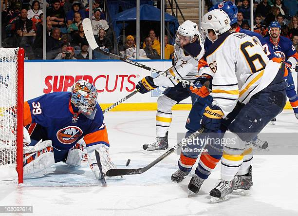 Goaltender Rick DiPietro of the New York Islanders makes a pad save as Luke Adam and Tyler Ennis of the Buffalo Sabres look for the roubound on...