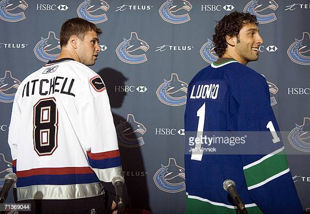 Goaltender Roberto Luongo and defenseman Willie Mitchell wear Vancouver Canuck jersies as they face the media for the first time since recently being...