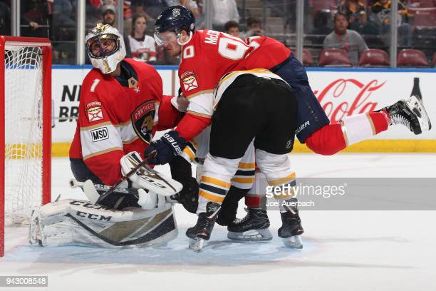 Goaltender Roberto Luongo defends the next as Jared McCann of the Florida Panthers checks Noel Acciari of the Boston Bruins at the BBT Center on...