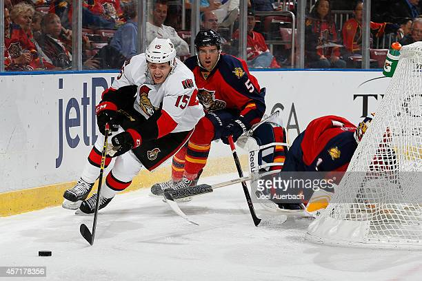Goaltender Roberto Luongo falls behind the net as Aaron Ekblad of the Florida Panthers defends against Zack Smith of the Ottawa Senators as he...