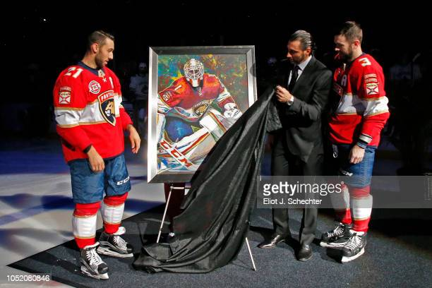 Goaltender Roberto Luongo in a black suit along with teammates Vincent Trocheck and Keith Yandle of the Florida Panthers unveils a portrait of...