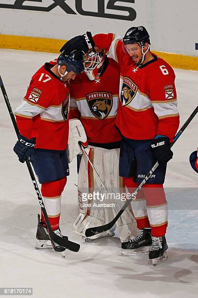 Goaltender Roberto Luongo is congratulated by Alex Petrovic and Derek MacKenzie of the Florida Panthers at the end of the game against the Colorado...