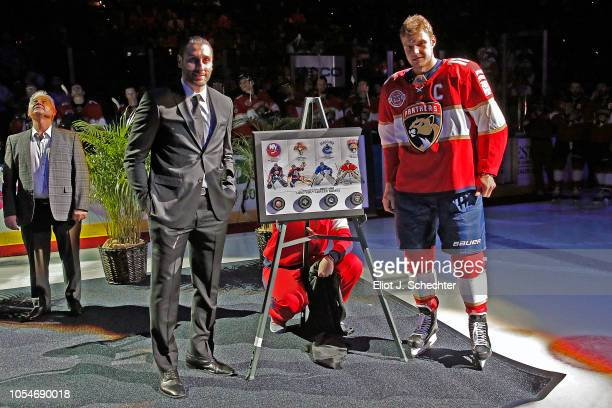 Goaltender Roberto Luongo is presented with a plaque filled with pucks by team Captain Aleksander Barkov during a celebration and commemoration of...