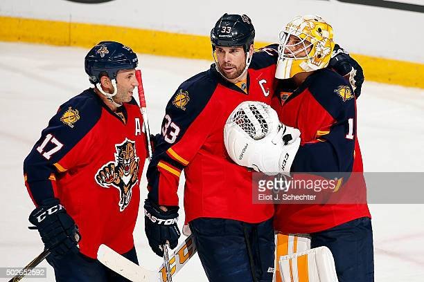 Goaltender Roberto Luongo of the Florida Panthers celebrates their win with teammates Willie Mitchell and Derek MacKenzie against the Columbus Blue...