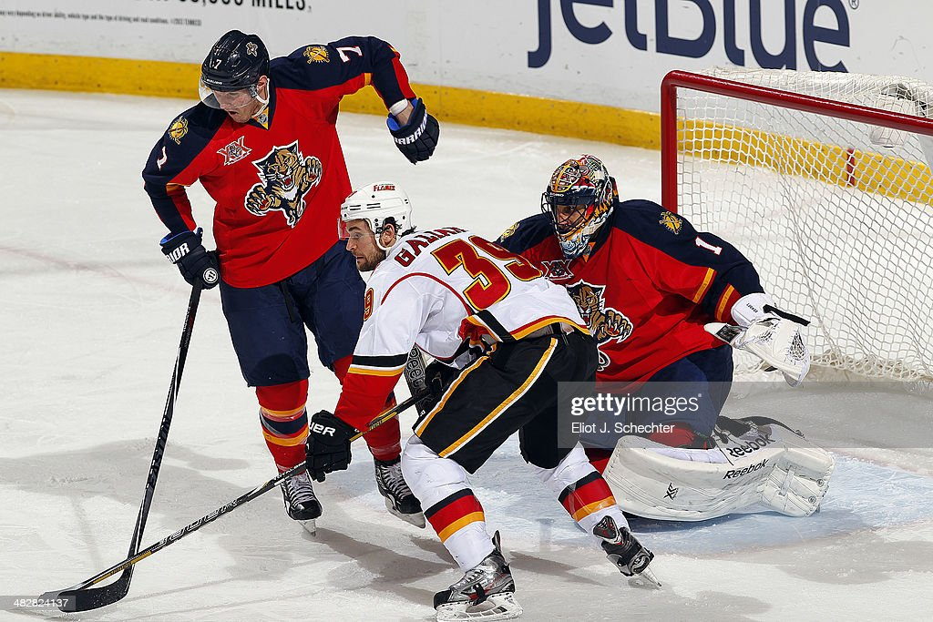 Goaltender Roberto Luongo #1 of the Florida Panthers defends the net with the help of teammate Dmitry Kulikov #7 against T.J. Galiardi #39 of the Calgary Flames at the BB&T Center on April 4, 2014 in Sunrise, Florida.