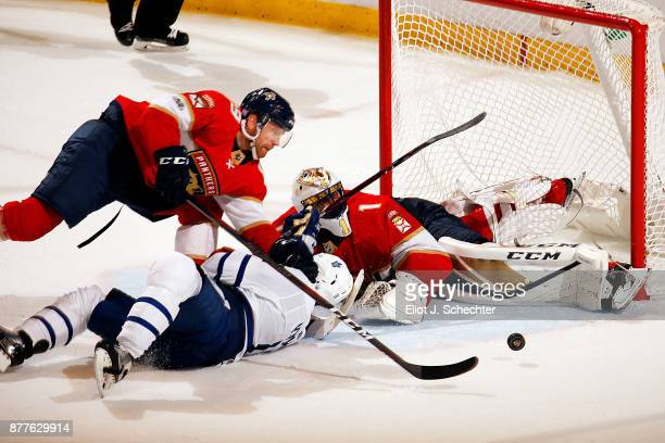 Goaltender Roberto Luongo of the Florida Panthers defends the net with the help of teammate Michael Matheson against Zach Hyman of the Toronto Maple...