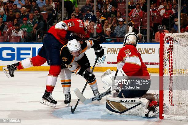 Goaltender Roberto Luongo of the Florida Panthers defends the net with the help of teammate Jared McCann against Noel Acciari of the Boston Bruins at...