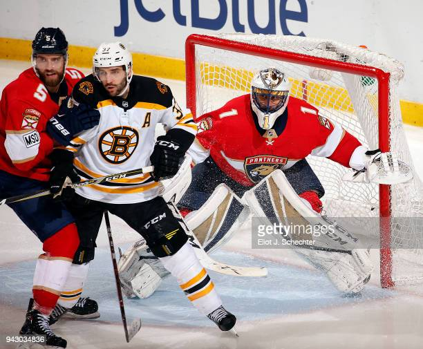 Goaltender Roberto Luongo of the Florida Panthers defends the net with the help of teammate Aaron Ekblad against Patrice Bergeron of the Boston...