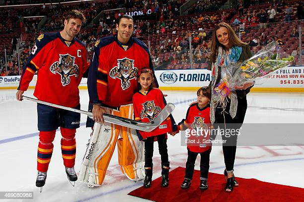 Goaltender Roberto Luongo of the Florida Panthers is honored before the game with fellow teammate Willie Mitchell along with his wife Gina and their...