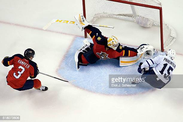 Goaltender Roberto Luongo of the Florida Panthers makes a glove save with teammate Steven Kampfer near by against PierreAlexandre Parenteau of the...