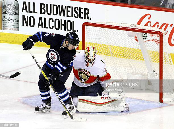 Goaltender Roberto Luongo of the Florida Panthers makes a save as Marko Dano of the Winnipeg Jets tries to deflect the puck into the net during...