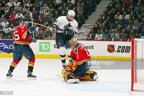 Goaltender Roberto Luongo of the Florida Panthers stops a shot with his arm as teammate Brad Ference watches Todd Bertuzzi of the Vancouver Canucks...
