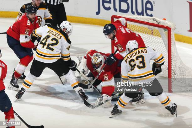 Goaltender Roberto Luongo of the Florida Panthers stops a shot with Brad Marchand and David Backes of the Boston Bruins attempting to get the rebound...