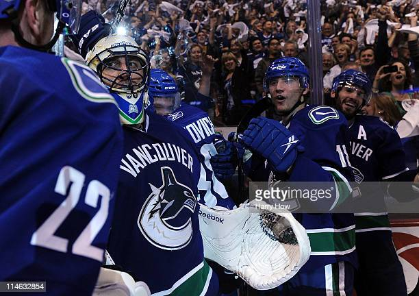 Goaltender Roberto Luongo of the Vancouver Canucks celebrates with teammates Daniel Sedin, Chris Tanev and Ryan Kesler after they defeated the San...