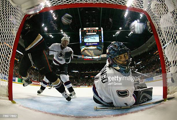 Goaltender Roberto Luongo of the Vancouver Canucks reacts after making a save as Chris Kunitz of the Anaheim Ducks crashes into the net during game...