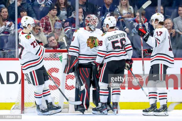 Goaltender Robin Lehner of the Chicago Blackhawks gets congratulated by teammates Kirby Dach Erik Gustafsson and Dylan Strome as they celebrate a 41...