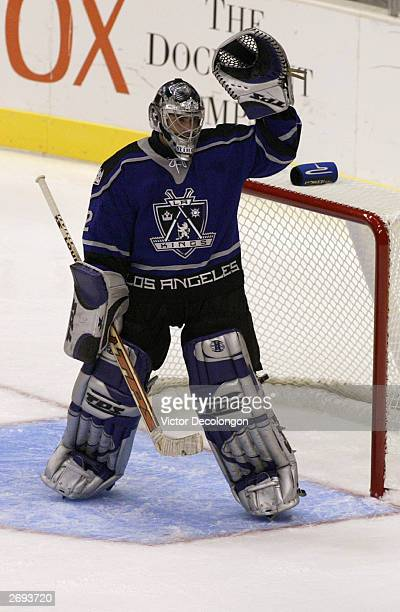 Goaltender Roman Cechmanek of the Los Angeles Kings raises his glove to signal to a teammate in the first period of a game against the Ottawa...