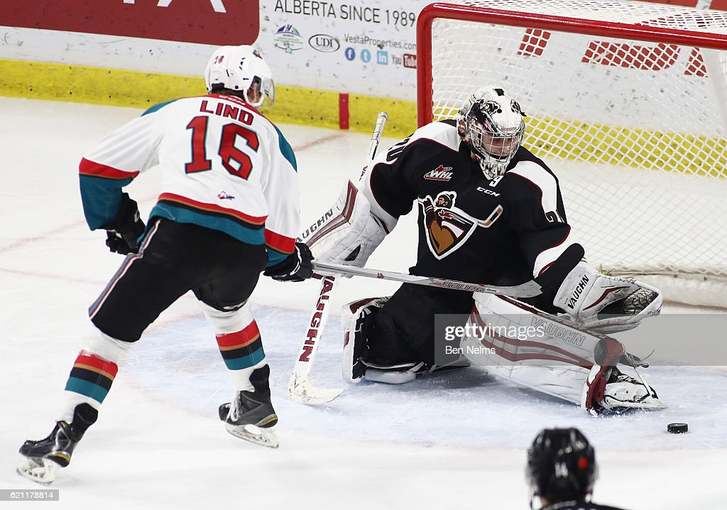 Goaltender Ryan Kubic #20 of the Vancouver Giants makes a save against Kole Lind #16 the Kelowna Rockets during the second period of their WHL game at the Langley Events Centre on November 4, 2016 in Langley, British Columbia, Canada.