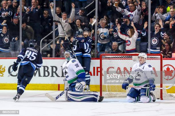 Goaltender Ryan Miller and Bo Horvat of the Vancouver Canucks sit dejectedly on the ice as Mathieu Perreault of the Winnipeg Jets joins teammates...