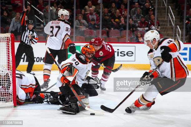 Goaltender Ryan Miller of the Anaheim Ducks makes a pad save as Nick Cousins of the Arizona Coyotes and Cam Fowler skate in during the first period...