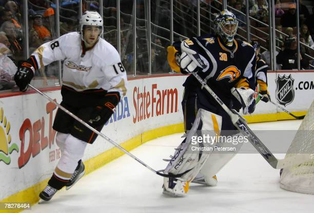 Goaltender Ryan Miller of the Buffalo Sabres clears the puck as his brother Drew Miller of the Anaheim Ducks skates by during the third period of the...