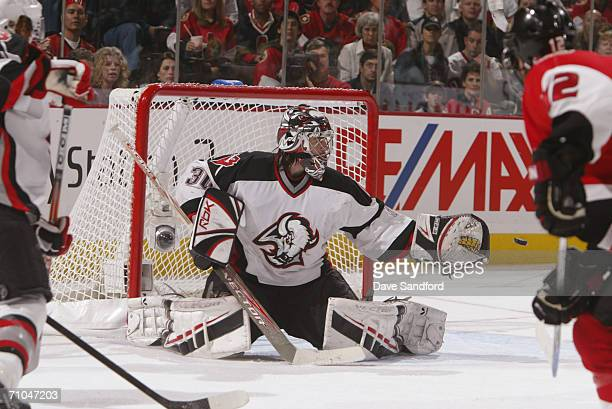 Goaltender Ryan Miller of the Buffalo Sabres reaches for the puck on a shot by the Ottawa Senators in game five of the Eastern Conference Semifinals...