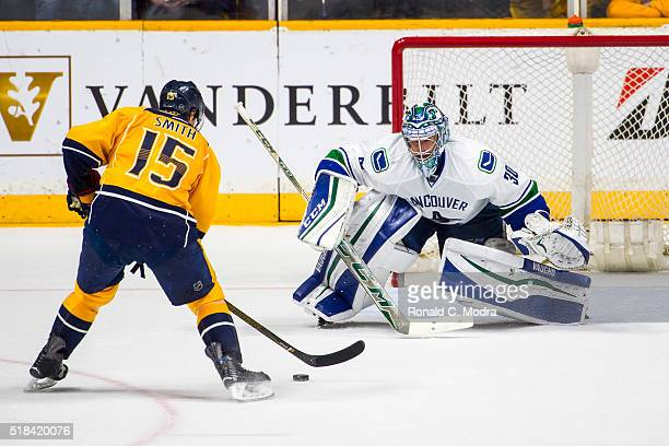 Goaltender Ryan Miller of the Vancouver Canucks tries to protect the net as Craig Smith of the Nashville Predators scores during a NHL game at...