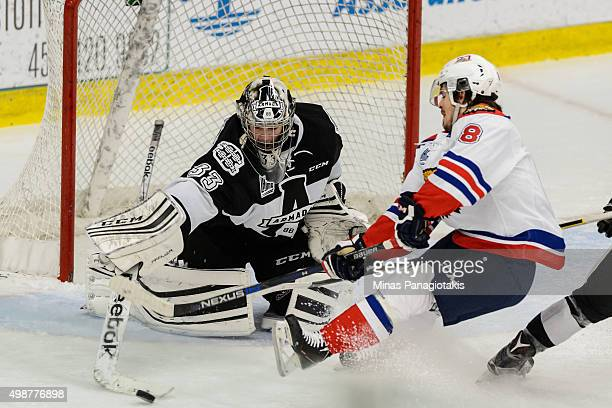 Goaltender Samuel Montembeault of the Blainville-Boisbriand Armada pokes the puck away from Conor Garland of the Moncton Wildcats during the QMJHL...