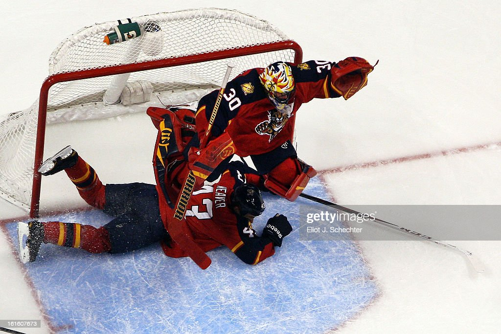 Goaltender Scott Clemmensen #30 of the Florida Panthers jumps out of the way of teammate Mike Weaver #43 against the Washington Capitals at the BB&T Center on February 12, 2013 in Sunrise, Florida.