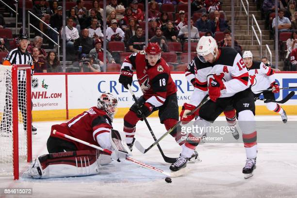 Goaltender Scott Wedgewood and Christian Dvorak of the Arizona Coyotes clear the puck from Travis Zajac of the New Jersey Devils during the second...