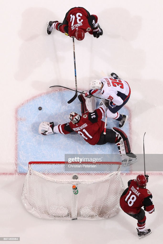 Goaltender Scott Wedgewood #31 of the Arizona Coyotes dives to cover the puck as Alex Chiasson #39 of the Washington Capitals and Zac Rinaldo #34 skate in during the third period of the NHL game at Gila River Arena on December 22, 2017 in Glendale, Arizona. The Coyotes defeated the Capitals 3-2 in overtime.