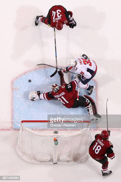 Goaltender Scott Wedgewood of the Arizona Coyotes dives to cover the puck as Alex Chiasson of the Washington Capitals and Zac Rinaldo skate in during...