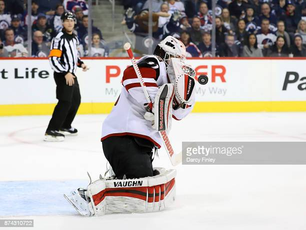 Goaltender Scott Wedgewood of the Arizona Coyotes reacts as the puck bounces of his blocker off a shot from a Winnipeg Jets during second period...