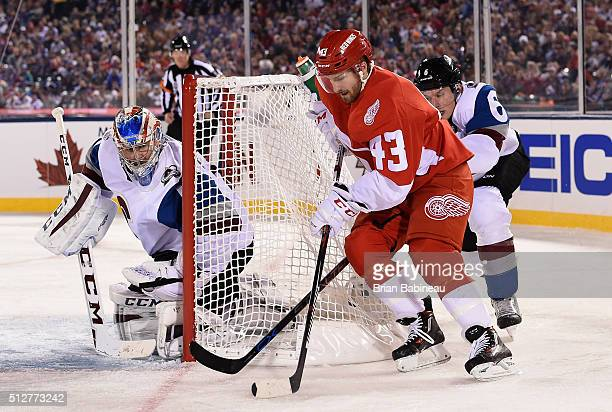 Goaltender Semyon Varlamov of the Colorado Avalanche defends his net as Darren Helm of the Detroit Red Wings brings the puck around the net in the...