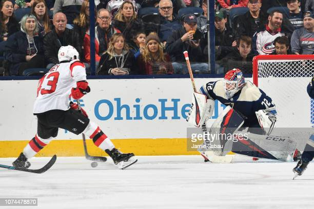 Goaltender Sergei Bobrovsky of the Columbus Blue Jackets defends the net as Brett Seney of the New Jersey Devils skates with the puck during the...