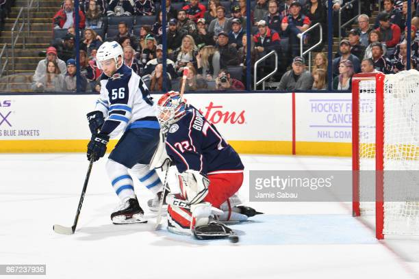 Goaltender Sergei Bobrovsky of the Columbus Blue Jackets defends the net as Marko Dano of the Winnipeg Jets reaches to redirect the puck during the...