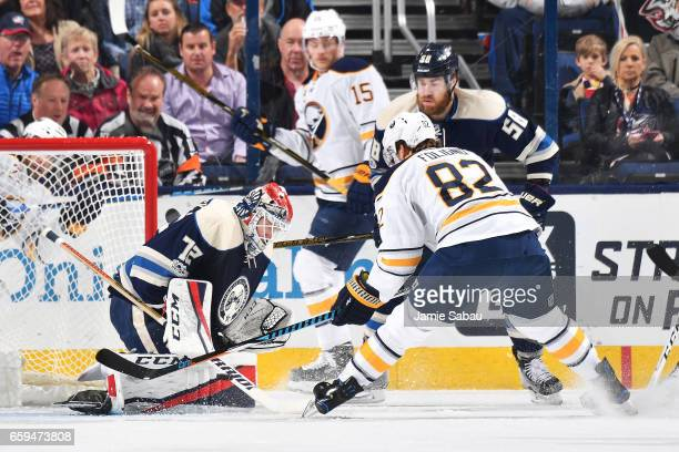 Goaltender Sergei Bobrovsky of the Columbus Blue Jackets freezes the puck as Marcus Foligno of the Buffalo Sabres and David Savard of the Columbus...