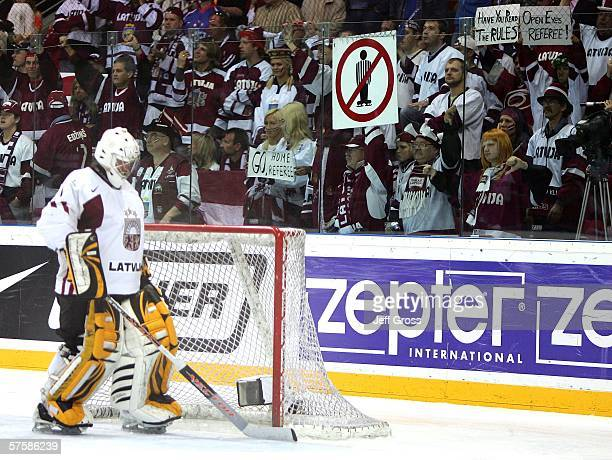 Goaltender, Sergejs Naumovs of Latvia waits for the ice to be cleaned after Latvian fans threw coins and bottles in opposition to the referee's calls...