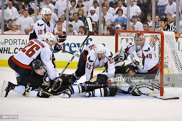 Goaltender Simeon Varlamov of the Washington Capitals is hemmed in the net after Shaone Morrisonn and Mike Green of the Capitals bring down Evgeni...