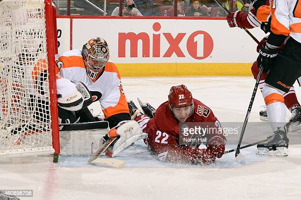 Goaltender Steve Mason of the Philadelphia Flyers tries to cover up the puck as Brandon McMillan of the Arizona Coyotes slides past the goal during...