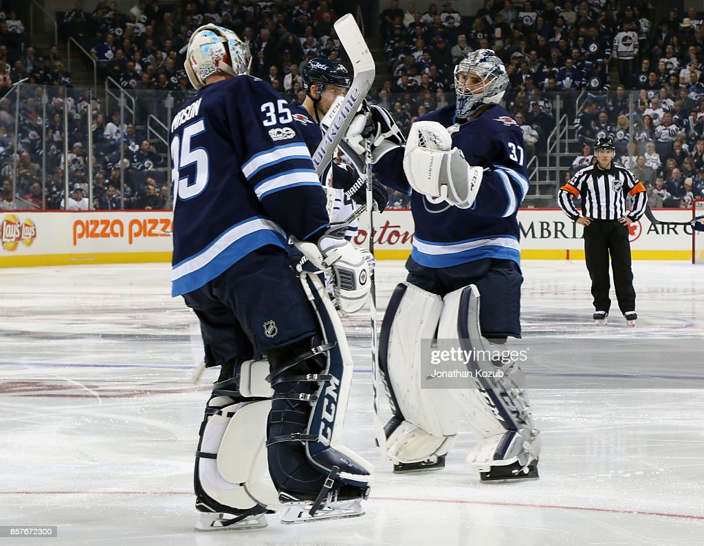 Goaltender Steve Mason #35 of the Winnipeg Jets exchanges glove taps with teammate Connor Hellebuyck #37 after being pulled during third period action against the Toronto Maple Leafs at the Bell MTS Place on October 4, 2017 in Winnipeg, Manitoba, Canada.