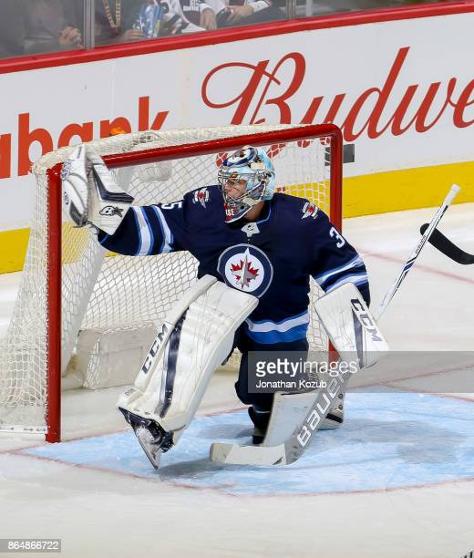 Goaltender Steve Mason of the Winnipeg Jets makes a glove save during second period action against the Columbus Blue Jackets at the Bell MTS Place on...