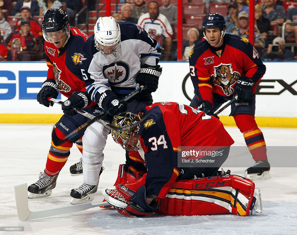 Goaltender Tim Thomas #34 defends the net with the help of teammate Dmitry Kulikov #7 against Matt Halischuk #15 of the Winnipeg Jets at the BB&T Center on December 5, 2013 in Sunrise, Florida.