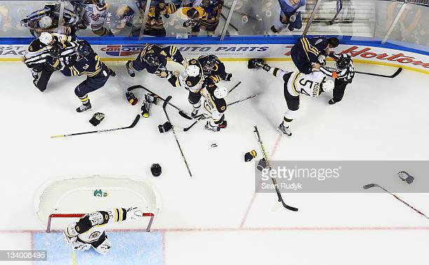 Goaltender Tim Thomas of the Boston Bruins watches as players from Buffalo Sabres and Boston Bruins square off during a first period fight at First...