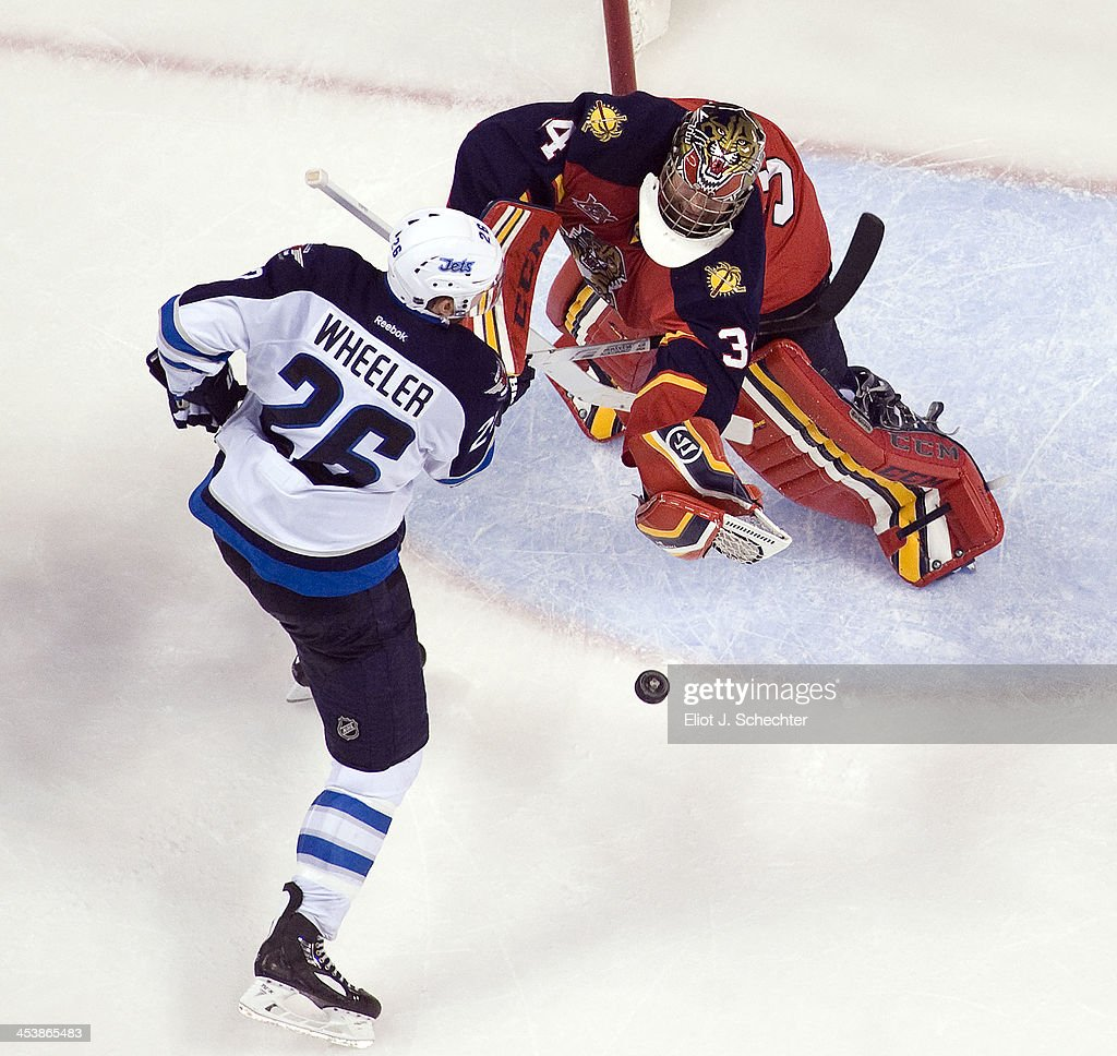 Goaltender Tim Thomas #34 of the Florida Panthers defends the net against Blake Wheeler #26 of the Winnipeg Jets at the BB&T Center on December 5, 2013 in Sunrise, Florida.