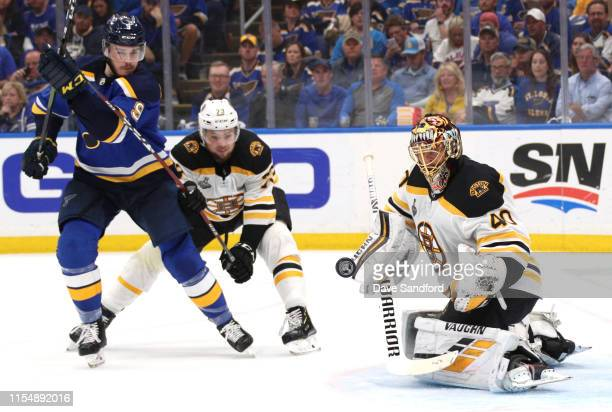 Goaltender Tuukka Rask of the Boston Bruins makes save as Sammy Blais of the St Louis Blues and Karson Kuhlman of the Boston Bruins vie for position...