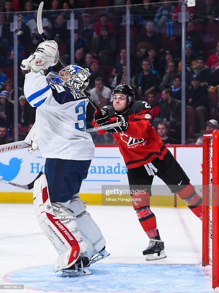 Goaltender Veini Vehvilainen of Team Finland #31 jumps for the puck as Mitchell Stephens #27 of Team Canada tries to knock it down with his stick during the IIHF exhibition game at the Bell Centre on December 19, 2016 in Montreal, Quebec, Canada. Team Canada defeated Team Finland 5-0.