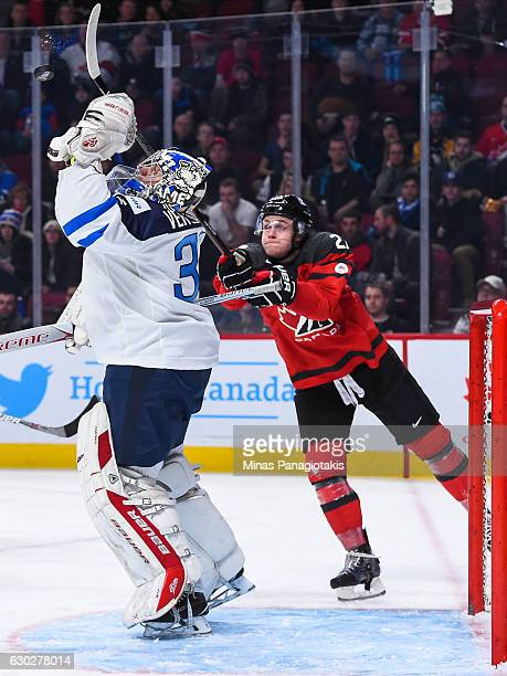 Goaltender Veini Vehvilainen of Team Finland jumps for the puck as Mitchell Stephens of Team Canada tries to knock it down with his stick during the...